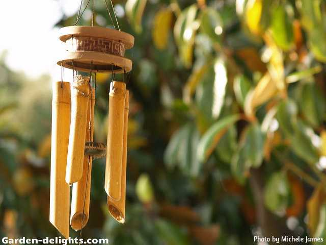 Bamboo wind chimes with five bells and a wooden striker with a ring top and carved decorations in the wood hanging topper hung in the tree with sunshine on one side, bamboo wind chime crafts, hanging windchimes, whimsical windchimes, wooden windchimes, breezy with music windchimes, Hawaiian bamboo chimes, sensory garden ideas, windchimes sun Dreamcatcher, garden windchimes, creating a natural look and appearance with beautiful wind music created by a soft breeze.