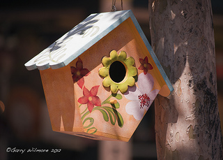 Small cute birdhouse with flowers on front and blue roof hanging in tree, unique birdhouses, birdhouse decorating.