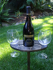 Brown Jordan Outdoor Furniture, small patio table with bottle of wine and two glasses on grass.