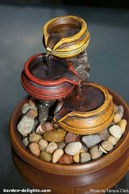 Small tabletop ceramic fountain with three small bowls pouring into each other that are yellow, red and orange with a rock base in a ceramic bowl that is a cordless fountain used for the patio table or inside your home or office, tabletop waterfalls, tiered tabletop fountains, fiberglass fountains, indoor water fountains, indoor tabletop water feature, tabletop Gardens, mini fountains, fountain ideas, desktop fountains create a visual motion and sensory sound of water allowing for a unique visual artistic theme.