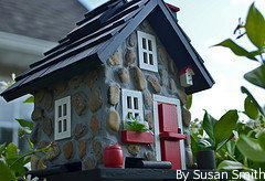 Cute birdhouse with red door white windows and a blue roof, funny birdfeeders, cute birdhouse picture.