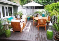 Outdoor deck/patio furniture sets, wooden outdoor furniture with patio umbrella on patio deck deck with blue cushions.