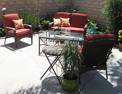 Discount Outdoor Furniture, Wicker loveseat with two chairs in red with coffee table and plant on top.