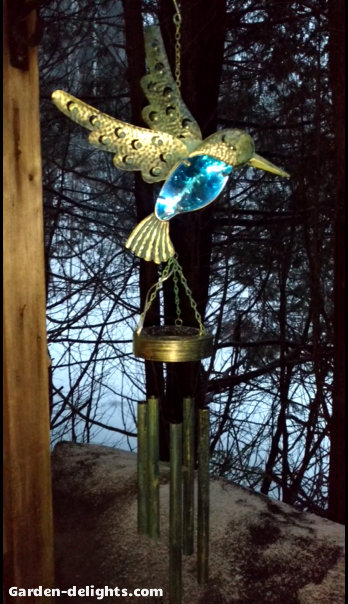 Gold bird with blue electric lights with rotating electric wind chimes on deck looking at trees, battery operated indoor wind chimes, indoor solar chimes, Walmart, solar powered tabletop wind chimes.