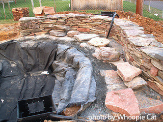 Flexible pond liner inside of dugout pond with shale stone stacked up like a wall along edge. Fecorative pond ideas, backyard water fe ature planning.