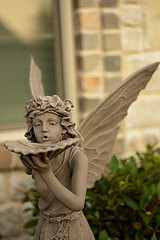 Stone fairy statue with wings holding a seashell up to her face, fantasy water features, solar powered fairy water fountains.