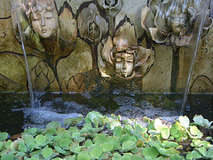 Mystical fairy faces on the front of wall fountain pouring water into lower basin with plants, ferry water fountains, fantasy fairy fountains.