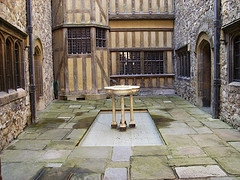 Water fountain basin sitting in the middle of castle courtyard with stone and wood walls, stone water fountains, indoor water fountains.