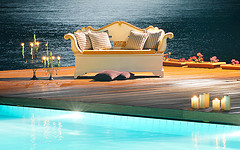 Outdoor Furniture Pillows, glamorous outdoor deck loveseat with straight pillows and candles in front of pool.