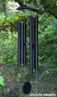 Black powder coated long tube windchimes with resin striker and black string hung on a tree, large windchimes, deep tone windchimes.