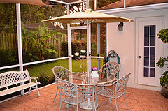 Metal outdoor furniture, white outdoor furniture set with umbrella on deck with palm trees.