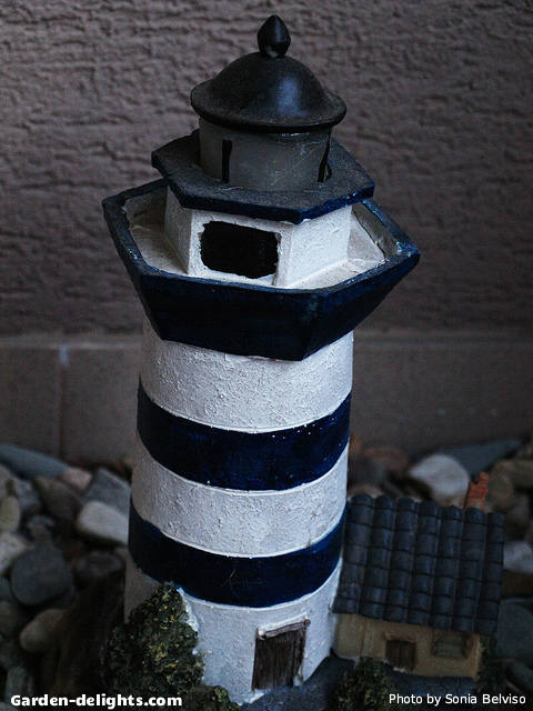 Miniature solar garden lighthouse with black and white stripes in a rock bed garden, solar garden light, outdoor lighthouse kits, Walmart, wooden lighthouses.