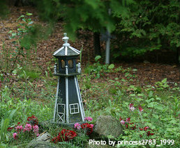 Incroyable Small Miniature Green Lighthouse Beside Rocks And Red Flowers With Windows  In Beacon Room, Outdoor