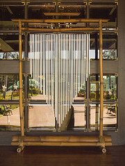 Long metal tube windchimes mounted to bamboo frame in courtyard, musical when tribes, bamboo wind chimes.