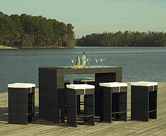 Outdoor Bar Furniture, Wicker bar set with five stools and white cushions with martini glasses on top in front of Lake.