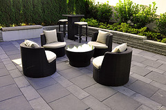 Outdoor furniture rugs, Brown Wicker patio furniture with coffee table and stand up bar with stools.