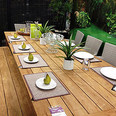 Outdoor Teak Furniture, teak dining table with placemats and plates with fruit on them.