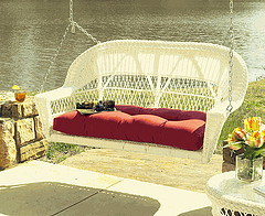 Outdoor Wicker garden furniture, white resin wicker swing chair in front of waterfront.