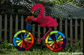 Pink flamingo wind spinner riding bike with colorful wheels, garden wind spinners, wind art.