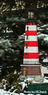 Red and white striped lighthouse with replica stone on bottom and black beacon with light, garden lighthouses, replica lawn lighthouses.