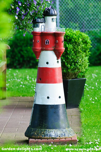 Small lighthouse on brick patio with black white and red striped with Castle top design and small windows, solar lighthouse with rotating beacon, lighthouse lawn ornament, lawn lighthouse with rotating solar beacon
