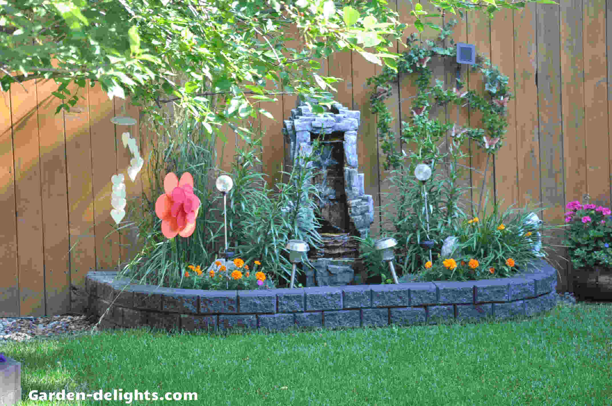 Stonewall water feature in flower bed surrounded by red tulips against Cedar fence, water fountain, Home Depot, large outdoor fountains, landscaping ideas, backyard planning, patios,Gardening insights, modern fountain, sleek fountain, water fountain ideas, garden water feature, small water features.