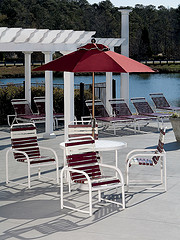 Discounted Outdoor Furniture, aluminum frame with plastic wrap red and white striped chairs with aluminum table and glass top and red umbrella.