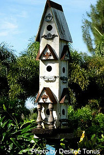 Tall white wooden birdhouse tower with tall roof peak and multiple bird hole entrances with front porch. Wooden birdhouses, decorative wood birdhouses