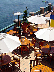 Teak Garden Furniture, teak outdoor furniture sets on restaurant balcony with patio heaters overlooking water.