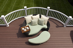 Outdoor Furniture Cushions, tear shaped loveseat and footstool with green and white patio cushions on deck overlooking backyard.
