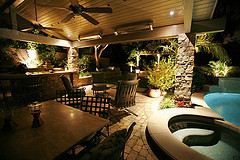 outdoor patio furniture sets, two patio sets by hot tub with bar and ceiling fans in outdoor patio living area.