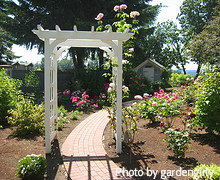 White Wooden Arbor With Red Brick Pathway Flowing Through In Rose Garden, Outdoor  Garden Arbors