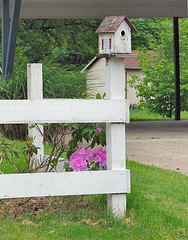 White wood birdhouse with red roof mounted on wooden fence post, decorative white birdhouses, unique birdhouses.