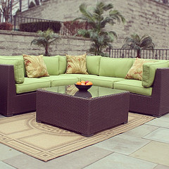 Wholesale Outdoor Furniture, Wicker sectional with lime green patio cushions and Wicker table with oranges in bowl.