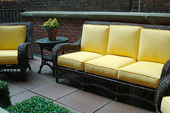 Wholesale Outdoor Furniture, Wicker outdoor couch with two chairs with yellow cushions and patio table with yellow flowers on top of table.