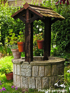 Stone finish wishing well with dark wood cedar shingles with small flowerpots, rustic wishing well,decorative wishing wells.