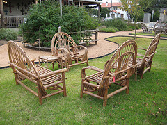 Delicieux Rustic Outdoor Furniture, Two Chairs And Loveseat Country Style Wooden  Chairs On Grass.