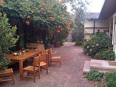 Cedar Wood Outdoor Furniture, wood table and six chairs on brick patio with trees overhanging.